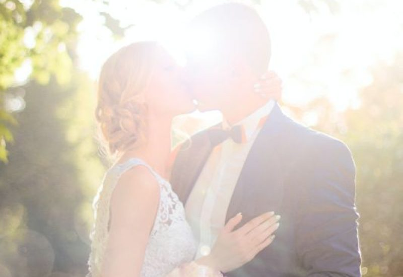 bride-and-groom-kissing-near-tree-against-the-sun-photo-1244700